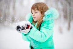 A menina funde a neve com os mitenes no parque bonito durante a queda de neve fotografia de stock royalty free