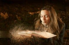 A menina funde a neve do livro aberto no parque do inverno Fotografia de Stock
