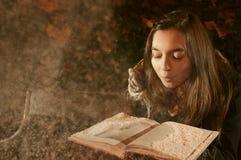A menina funde a neve do livro aberto no parque do inverno Fotos de Stock Royalty Free