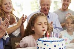 A menina funde para fora velas do bolo de aniversário no partido da família imagem de stock royalty free
