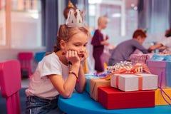 Menina furada do aniversário que sonha para olhar seus presentes fotografia de stock royalty free