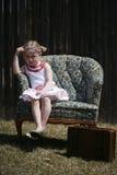 Menina furada que senta-se em uma cadeira fotografia de stock
