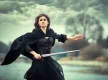 A menina gótico bonita com espada imagens de stock