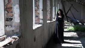 Menina gótico da bruxa que anda ao lado das janelas arruinadas em uma mansão destruída velha filme