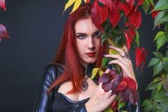 Menina gótico principal vermelha bonita que veste o equipamento de couro preto e que guarda e que abraça as folhas de outono das  fotografia de stock royalty free