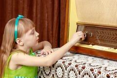 A menina gerencie o botão do volume no rádio velho Estilo retro imagem de stock royalty free