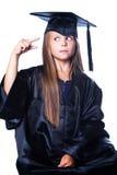 Menina Gesticulating no vestido da graduação no isolado Fotos de Stock