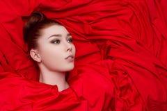 Menina glamoroso bonita no pano vermelho Fotos de Stock
