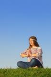 A menina gorda meditates e pensa na grama verde imagens de stock