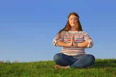 A menina gorda nas calças de brim senta-se na grama e meditates imagem de stock royalty free