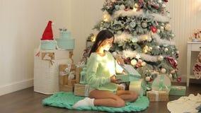 A menina grávida abre um presente de incandescência do Natal filme