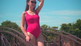 Menina grávida bonita em um roupa de banho de uma peça só vermelho e suportes dos vidros em uma ponte perto da associação video estoque