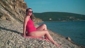 A menina grávida bonita em um roupa de banho de uma peça só vermelho e em vidros senta-se na praia filme