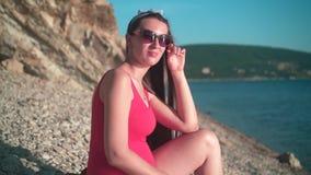 A menina grávida bonita em um roupa de banho de uma peça só vermelho e em vidros senta-se na praia vídeos de arquivo