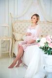 A menina grávida bonita em uma casa veste o assento no interior em uma cama de rosas imagem de stock royalty free
