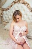 A menina grávida bonita está sentando-se no interior com mobília italiana luxuoso e está abraçando-se a barriga Fotos de Stock