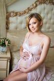 A menina grávida bonita está sentando-se no interior com mobília italiana luxuoso e está abraçando-se a barriga Imagem de Stock Royalty Free