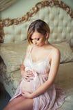 A menina grávida bonita está sentando-se no interior com mobília italiana luxuoso e está abraçando-se a barriga Foto de Stock Royalty Free
