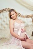 A menina grávida bonita está sentando-se no interior com mobília italiana luxuoso e está abraçando-se a barriga foto de stock