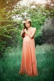 Menina grávida bonita nova com cabelo marrom longo no vestido do pêssego com a grinalda da flor em sua cabeça Imagem de Stock