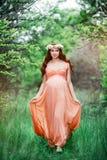 Menina grávida bonita nova com cabelo marrom longo no vestido do pêssego com a grinalda da flor em sua cabeça que anda no jardim Foto de Stock Royalty Free