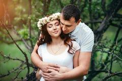 Menina grávida bonita nova com seu marido com o urso do brinquedo no jardim verde Fotos de Stock