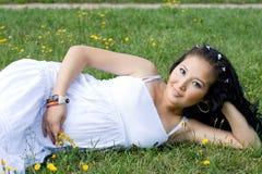 Menina grávida bonita que encontra-se na grama Fotografia de Stock Royalty Free