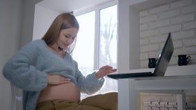 Menina grávida com um portátil que senta-se em uma tabela no luminoso e que afaga sua barriga despida em casa video estoque