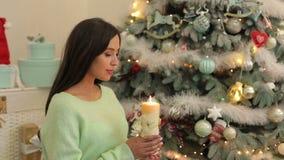 Menina grávida com vela perto da árvore de Natal video estoque
