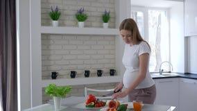 A menina grávida come o abacate e corta vegetais com a faca em suas mãos que estão na mesa de cozinha video estoque
