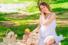 Menina grávida dos jovens em um branco sarafan em uma manta em um parque Foto de Stock Royalty Free