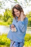 Menina grávida dos jovens em um branco sarafan em uma manta em um parque Fotografia de Stock