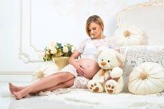 Menina grávida dos jovens que senta-se perto do sofá branco com urso de peluche e que olha a barriga grávida fotografia de stock royalty free