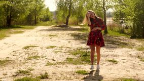 Menina grávida em caminhadas do vestido através da madeira video estoque