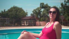 A menina grávida em um roupa de banho de uma peça só vermelho e em vidros senta-se perto da associação vídeos de arquivo