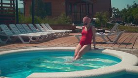 A menina grávida em um roupa de banho de uma peça só vermelho e em vidros senta-se perto da associação com seus pés para baixo na filme