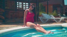 A menina grávida em um roupa de banho de uma peça só vermelho e em vidros senta-se perto da associação e do jogo com seus pés na  vídeos de arquivo
