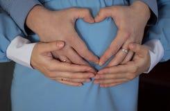 A menina grávida em um vestido azul com coração das mãos Fotografia de Stock Royalty Free