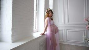 A menina grávida está perto de uma janela em um vestido cor-de-rosa bonito filme