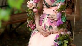 A menina grávida no vestido afaga sua barriga, close-up filme