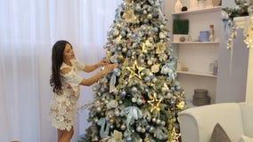 A menina grávida no vestido decora uma árvore de Natal filme