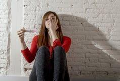 Menina grávida preocupada assustado do adolescente ou mulher desesperada nova que guardam o teste de gravidez positivo Fotos de Stock Royalty Free