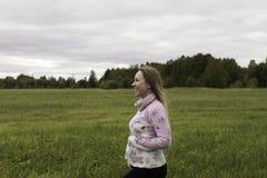 Menina grávida que anda na natureza e no sorriso Foto de Stock