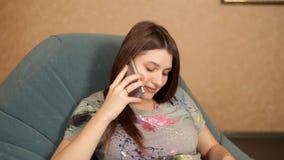 Menina grávida que senta-se em uma poltrona pela chaminé e que fala no telefone video estoque