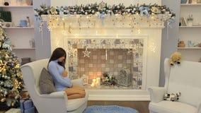 Menina grávida que senta-se na cadeira perto da árvore de Natal video estoque
