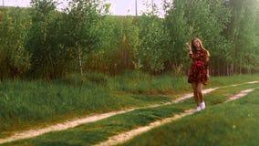 Menina gr?vida em caminhadas do vestido atrav?s da madeira vídeos de arquivo