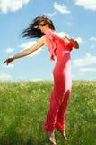 Menina graciosa de salto e de voo no fundo do céu azul imagens de stock