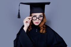 Menina graduada no tampão e no envoltório acadêmicos quadrados Fotografia de Stock
