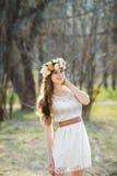 Menina, grinalda floral e floresta da mola Imagens de Stock Royalty Free