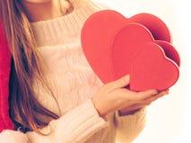 A menina guarda caixas de presente dadas forma coração Fotos de Stock Royalty Free